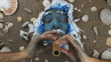 Blue sea man playing flute underwater