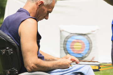 Man with spinal cord injury preparing bow and arrow