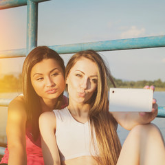 Two sporty young women taking a selfie outdoors in summer
