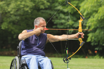 Man with spinal cord injury aiming his bow and arrow