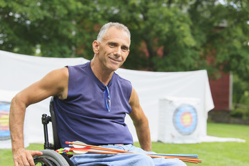 Man with spinal cord injury in wheelchair at archery practice