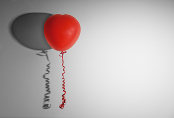 Red balloon in the shape of heart on the gray wall
