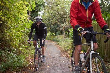 Two Mature Male Cyclists Riding Bikes Along Path