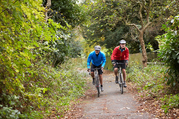 Two Mature Male Cyclists Riding Bikes Along Path