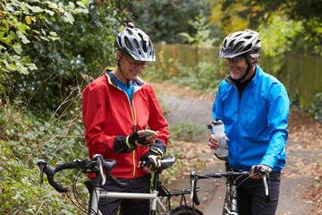 Two Mature Male Cyclists On Ride Looking At Mobile Phone App
