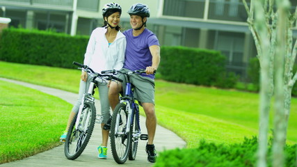 Happy Multi Ethnic Couple Activity Cycling Together Outdoors