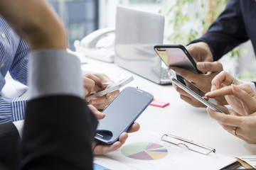 Four people who have a meeting with a mobile phone