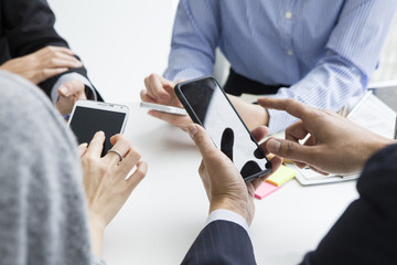 Four people using the mobile phone has a meeting