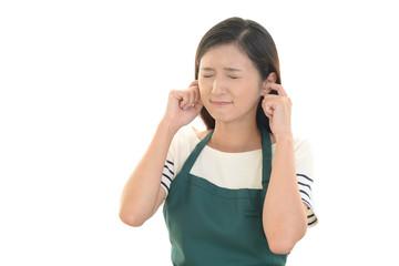耳をふさぐ女性