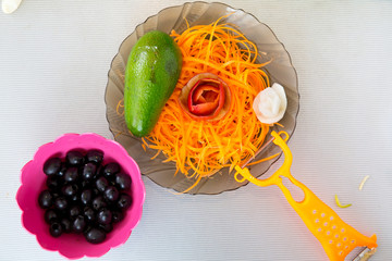 Straw carrot, avocado, rosette of apple and a plate of olives