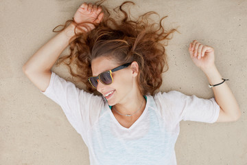 beautiful young woman lying on the sand with sunglasses