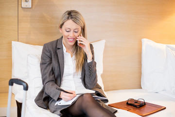 Business woman in hotel room talking on phone