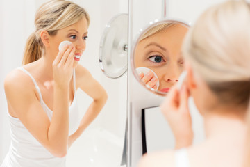 Young woman removing makeup in bathroom