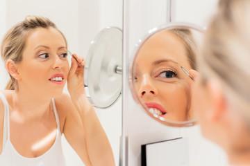 Young woman tweezing eyebrows in bathroom