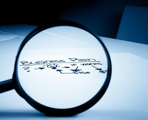business plan words see through lens of loupe on office table