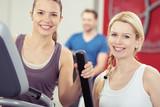 Fototapety zwei lächelnde frauen trainieren im fitness-center