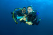 Happy couple scuba diving together - 76966182
