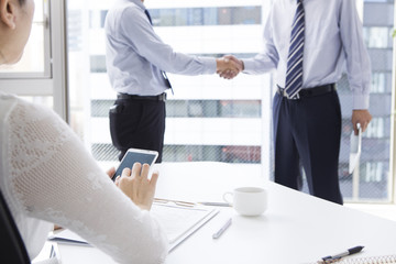 Woman looking at the handshake to have businessman