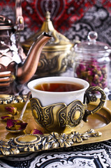 Tea roses in a beautiful Cup with Oriental motifs