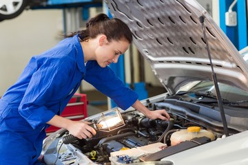 Mechanic examining under hood of car with torch