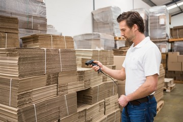 Serious warehouse worker holding scanner