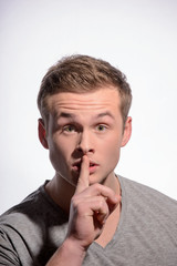 Young man with finger on his mouth