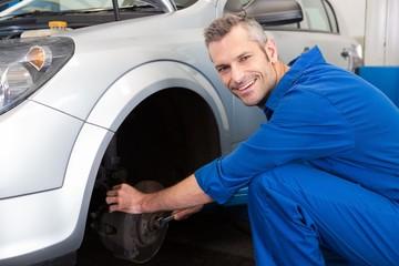 Smiling mechanic adjusting the wheel