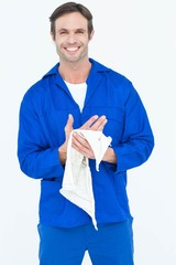 Confident mechanic wiping hand with napkin