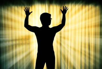 Silhouette of man surrendering with two hands raised in air