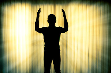 Silhouette man pray with light ray effect background