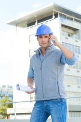 Architect using mobile phone outside building