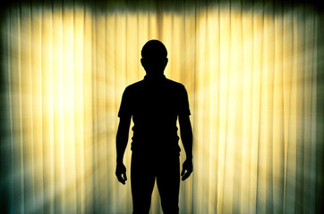 Silhouette of man standing with light ray effect background