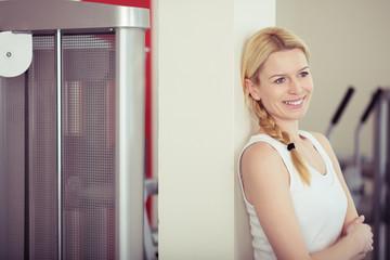 attraktive blonde frau steht entspannt im fitness-studio