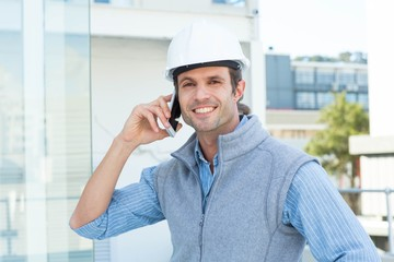 Smiling male architect using mobile phone outdoors