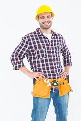 Handyman wearing tool belt while standing hands on hips