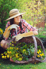 Beautiful gardener posing with basket full of flower