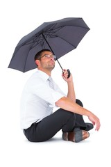 Businessman sitting on the floor with black umbrella