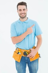Happy carpenter pointing against white background