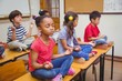 Pupils meditating in lotus position on desk in classroom - 76968763
