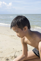 Asian Thai boy playing sand