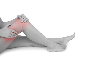 Mid section of young woman  touching her injured knee