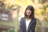 秋の紅葉した公園で立っている女性