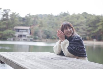 公園のテーブルに肘を付くニットセーターを着た女性