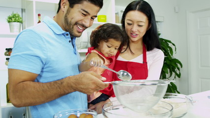 Young Ethnic Parents Happy Infant Daughter Home Kitchen Baking