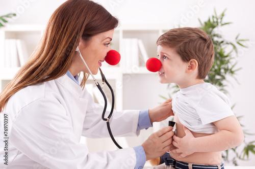 Smiling adorable female doctor clown listen patient heart - 76970397