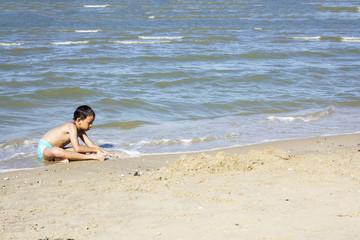 Asian Thai boy playing sand