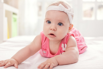 Cute baby girl in pink with white tie
