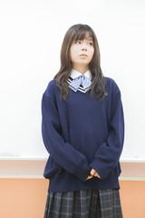 ホワイトボードの前で考える女子高生
