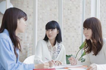 椅子に座ってノート見せ合う女子学生
