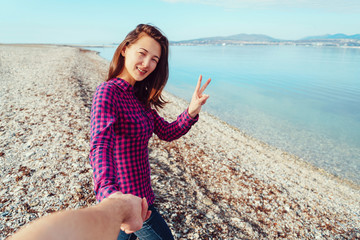 Young woman holding man's hand and showing peace sign
